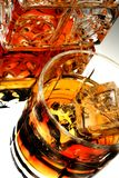 Whiskey Decanter and Glass. The side of an open ornate whiskey decanter and a glass of ice with liquor Stock Images