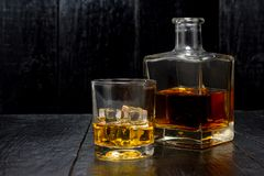 Whiskey with ice. Whiskey with a decanter on a wooden background Royalty Free Stock Image