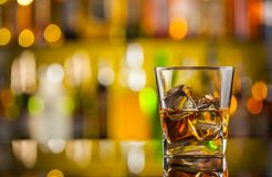 Whiskey drink on bar counter. With blur botles on backgorund Stock Photography