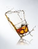 Whiskey drink with splash and ice cubes Stock Images