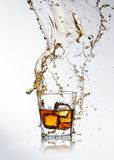 Whiskey drink with splash and ice cubes Stock Photos
