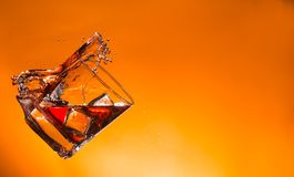 Whiskey drink with splash and ice cubes Royalty Free Stock Photos