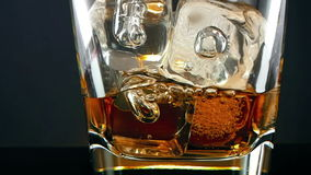 whiskey in the drinking glass with ice cubes on black background, time of relax drink with whisky