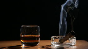 Whiskey drinks with smoking cigars stock footage
