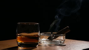 Whiskey drinks with smoking cigars