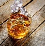 Whiskey et glace dans un verre transparent sur un fond en bois photo stock