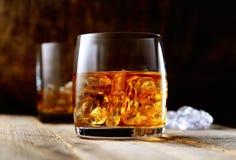 Whiskey et glace dans un verre transparent sur un fond en bois Images libres de droits