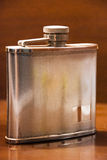 Whiskey flask. A whiskey flask on a wooden backgroud Stock Images