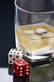 Whiskey and Gambling. A glass of Whiskey and dice as symbols of gambling Stock Image