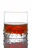 Whiskey glass. A whiskey glass reflected on white background Royalty Free Stock Photo