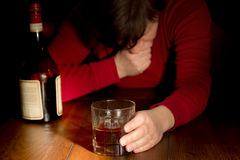 Whiskey Glass. Distraught woman holding a whiskey glass Stock Images