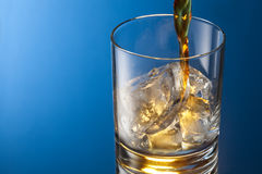 Whiskey glass. On a blue background Royalty Free Stock Image