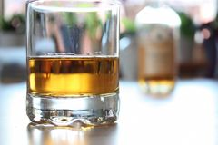 Whiskey Glass. A glass of whiskey with a bottle in the backdrop Stock Images
