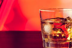 Whiskey glass on bar table with ice with space for text Stock Photography