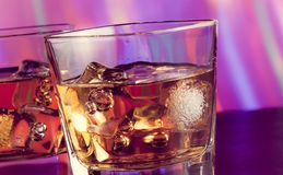 Whiskey glass on bar table with ice on warm atmosphere Royalty Free Stock Photos