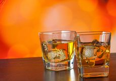 Whiskey glass on bar table with ice on warm atmosphere Royalty Free Stock Photo