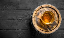 Whiskey in a glass on a barrel. On black rustic background royalty free stock images