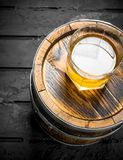 Whiskey in a glass on a barrel. On black rustic background stock image
