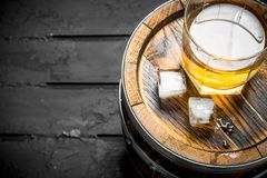 Whiskey in a glass on a barrel. On black rustic background royalty free stock photo