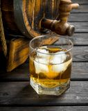 Whiskey in a glass and a barrel. On black wooden background stock image