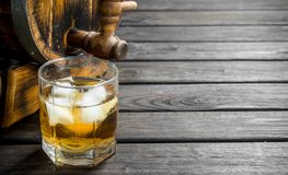 Whiskey in a glass and a barrel. On black wooden background stock photos
