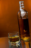 Whiskey glass and bottle Stock Images