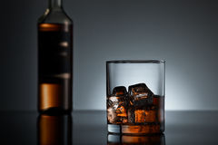 Whiskey glass and bottle. Whiskey glass with a bottle in background on black surface Royalty Free Stock Images
