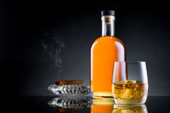 Whiskey glass, bottle and cigar on black surface Royalty Free Stock Photography
