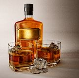 Whiskey. In the glass bottle and two glasses Royalty Free Stock Image