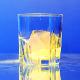Whiskey glass with burning ice on dusty table Royalty Free Stock Photo