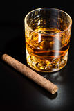 Whiskey glass and cigar. On black background Stock Photography