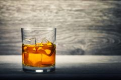 Whiskey glass and ice on wooden background. Whiskey in a glass filled with ice on a wooden bar table Stock Photos