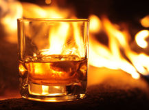 Whiskey Glass and Flames. Whiskey glass in front of striking flames of burning timbers Stock Photography