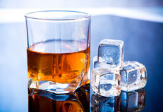 Whiskey in glass with ice cubes Royalty Free Stock Photos