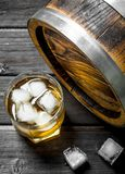 Whiskey in a glass with ice cubes and a barrel. On wooden background stock image