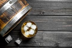 Whiskey in a glass with ice cubes and a barrel. On wooden background stock photography