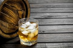 Whiskey in a glass with ice cubes and a barrel. On wooden background stock images