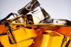 Whiskey glass with ice cubes close-up. Whiskey in glass with ice cube. On the rock Stock Photos