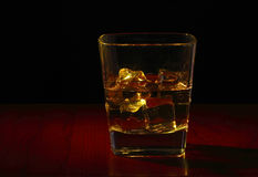 Whiskey glass on the table. Whiskey glass with ice cubes on the red wooden table Royalty Free Stock Image