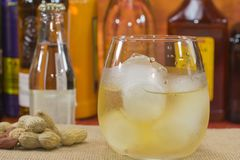 Whiskey with ice. Whiskey glass with ice in front of bottles, peanuts on the table Royalty Free Stock Photos