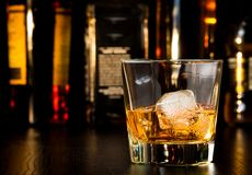 Whiskey glass with ice in front of bottles Stock Photography