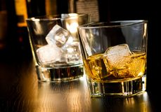 Whiskey glass with ice in front of empty whiskey glass Royalty Free Stock Images