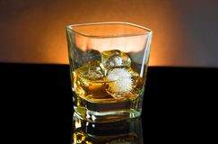 Whiskey glass with ice and warm light on black background Stock Photography