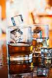 Whiskey glass with ice and warm light on black table with reflection, warm atmosphere Stock Photo