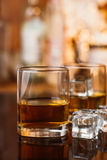 Whiskey glass with ice and warm light on black table with reflection, warm atmosphere Royalty Free Stock Photos