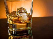 Whiskey glass with ice and warm light black table, warm atmosphere Royalty Free Stock Photography