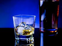 Whiskey glass near bottle on light tint blue disco Royalty Free Stock Photos
