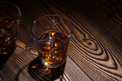 Whiskey in glass. Old texture of the board Royalty Free Stock Photography