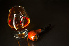 Whiskey glass and smoking pipe on black background. Cognac glass. Brandy glassful. Cognac france. Scotch drink. Smoking pipe stock photos