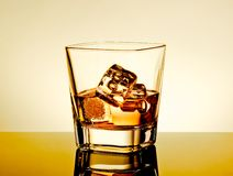 Whiskey in the glass on table with reflection, warm tint atmosphere Royalty Free Stock Image